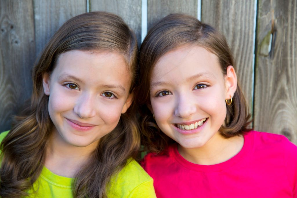 Happy twin sisters with different hairstyle smiling on